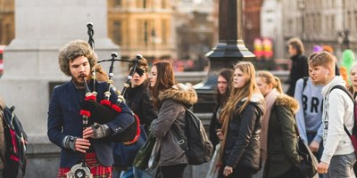 Man playing bagpipes in public, standing out in the crowd